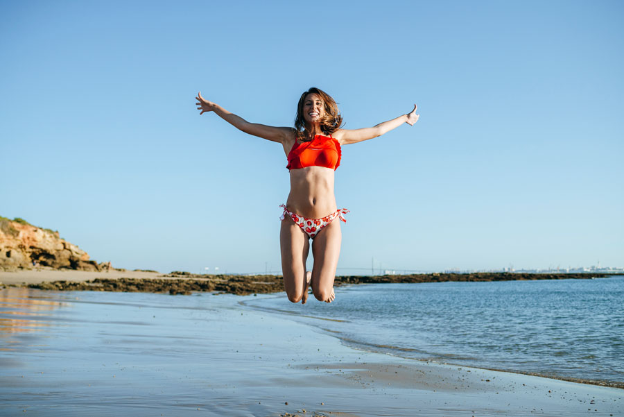 Young woman on beach in bikini jumping